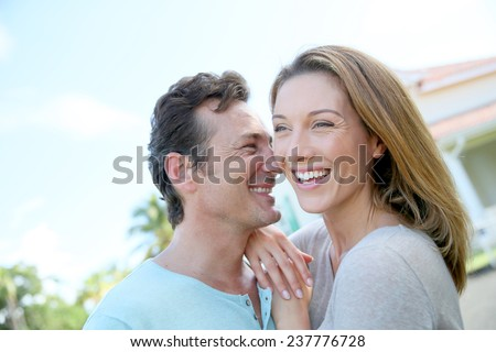 Cute loving couple standing in front of home and laughing - stock photo
