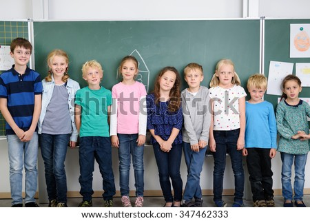 Cute Male and Female Kids Standing Against Green Chalkboard Inside the Classroom.