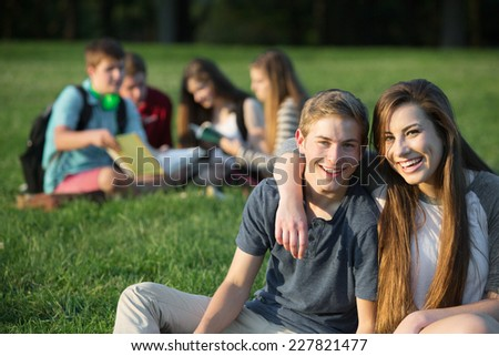 Cute male and female teens outdoors embracing