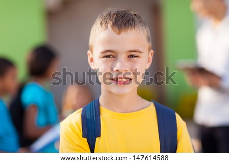 cute male elementary pupil outside classroom - stock photo