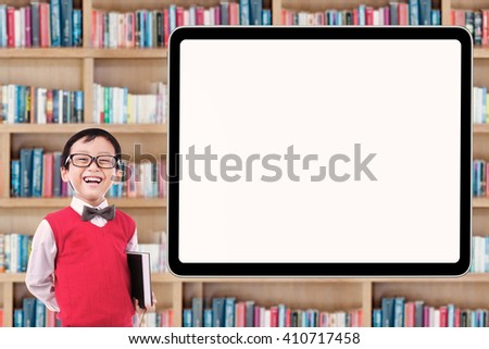 Cute male elementary school student standing in the library while laughing near the whiteboard - stock photo