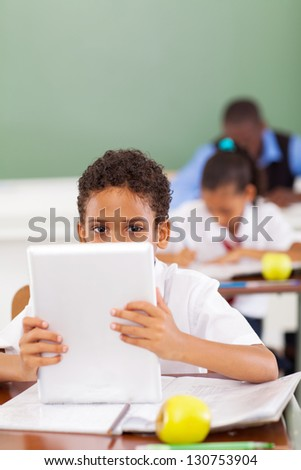 cute male elementary school student using tablet computer in classroom