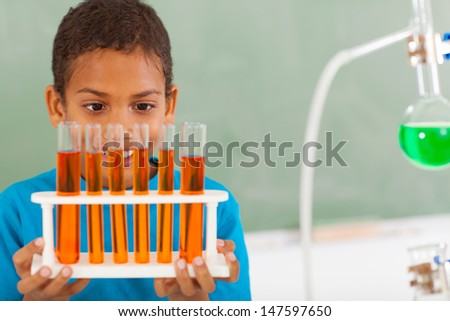 cute male primary school student in science class holding tubes - stock photo