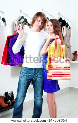 cute man and the woman in shop choose clothes - stock photo