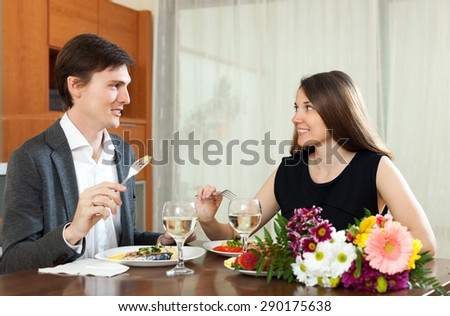 Cute man and woman having romantic dinner in home