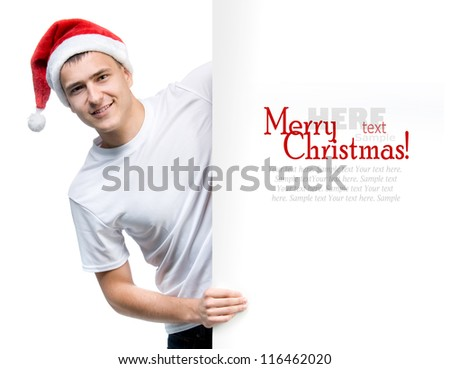 cute man in a Santa Claus hat behind the white board with space for text - stock photo