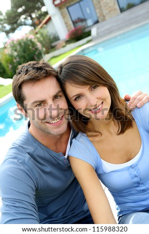 Cute married coule sitting in front of their new home - stock photo