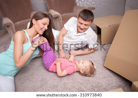 Cute married couple and their child are lying on flooring near boxes. A husband and wife are tickling their daughter with fun. They are smiling - stock photo
