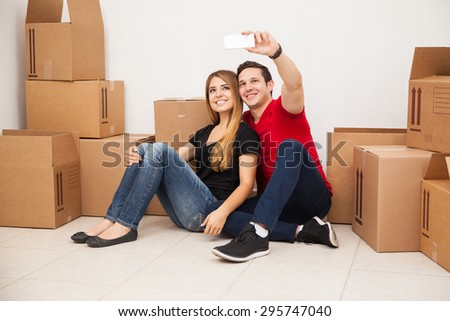 Cute married young couple having fun while moving to their new home and taking a selfie