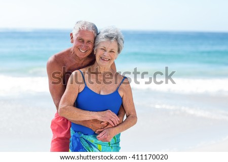 Cute mature couple embracing on the beach on a sunny day - stock photo