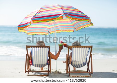 Cute mature couple lying on deckchairs on the beach - stock photo