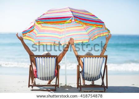 Cute mature couple raising arms on deckchairs on the beach - stock photo