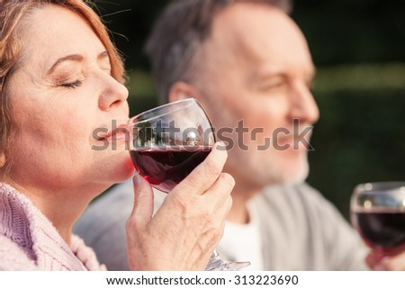 Cute mature husband and wife are drinking wine with joy. They are sitting on grass and smiling. The woman is smelling red drink. She closed her eyes with enjoyment - stock photo