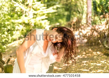 cute mature woman holds her head in a horizontal position while hair is dangling