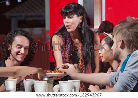 Cute mature woman sharing pizza with young group