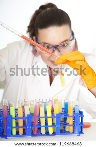 Cute medical or scientific researcher- chemist- scientist using a pipette and test tubes in a laboratory- selective focus