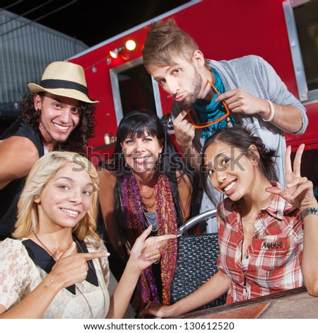 Cute men and women sitting in front of food truck - stock photo