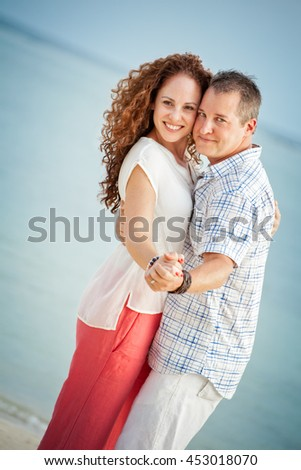 Cute middle aged couple dancing cheek to cheek on the beach - stock photo