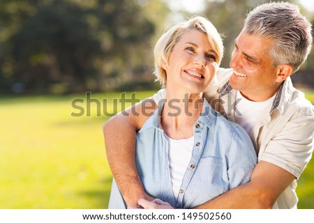 cute middle aged couple embracing outdoors  - stock photo