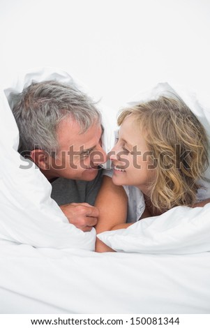 Cute middle aged couple under the duvet in bedroom at home - stock photo
