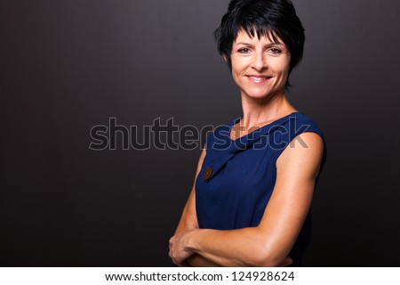 cute middle aged woman portrait on black - stock photo