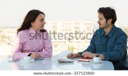 Cute Mix-Race Female Headhunter Listening Young Asian Candidate Casual Clothing Open Space Round Table with Laptop Notepad Hand notes and Coffee Mugs - stock photo