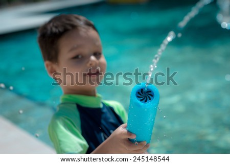 Cute mixed race Asian Caucasian boy happily plays with a water gun in a backyard swimming pool in the summer sun (shallow focus on the water gun) - stock photo