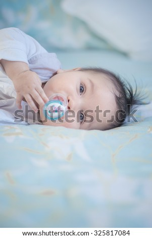 Cute mixed race Asian Caucasian 6 month old baby boy sucking a dummy plays inside on a bed - stock photo
