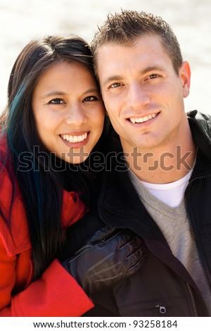 Cute mixed race couple portrait out in the snow - stock photo