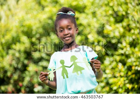 Cute mixed-race girl holding a paper tinsel on a park