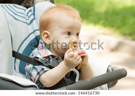 Cute 9 month baby boy chewing on toy sitting in stroller - stock photo