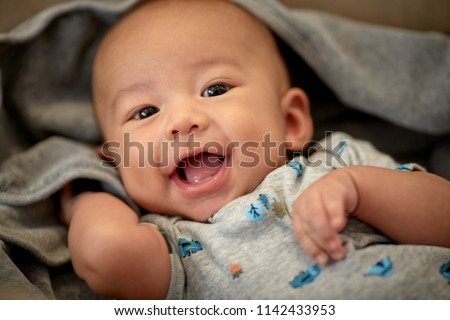 Cute 3 month old baby boy smiling with shallow depth of field