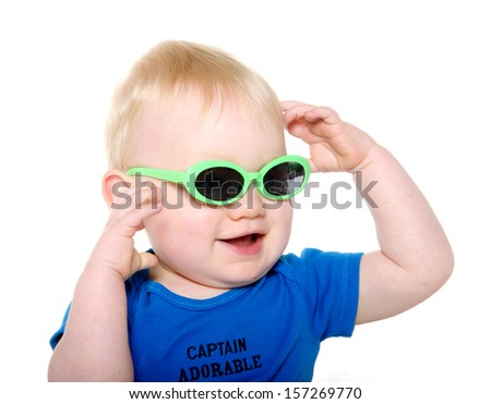 Cute 18-month-old baby boy with blond hair and blue shirt wearing green sunglasses on white background - stock photo