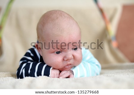 Cute 1,5 month old Caucasian baby boy with short blonde hair wearing a bright cloth and lying on his front on a bed - stock photo