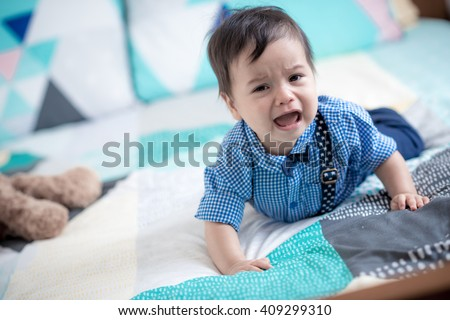 Cute 11 month old mixed race Asian Caucasian baby boy dressed up with braces and bow tie cries sadly on a colourful geometric shaped bed cover with his brown teddy bear in the background - stock photo