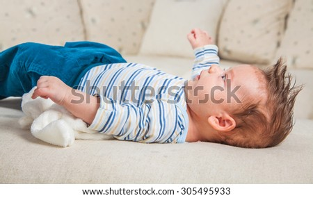 Cute 2 months old baby boy at home laying on his back on the sofa.