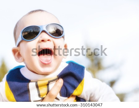 Cute 6 months old baby with Light brown hair in white, blue and brownish long-sleeved shirt wearing blue googles is embraced and held by his mum: he seems very happy and smiles