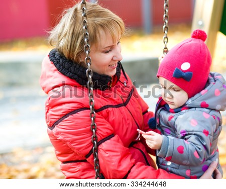 Cute mother and daughter playing on playground