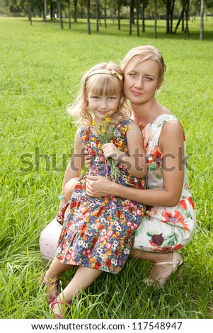 Cute mother and her daughter on summer meadow