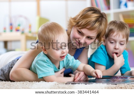 Cute mother and her two sons children reading together