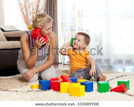 cute mother and kid boy playing together indoor - stock photo