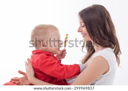 Cute mother is embracing her son and smiling. She is sitting and holding him. The boy is showing a large lollipop to her and laughing. Isolated on background