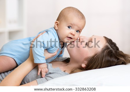 Cute mother kissing baby lying on bed in nursery - stock photo