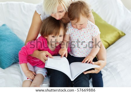 Cute mother reading a book with children on sofa - stock photo