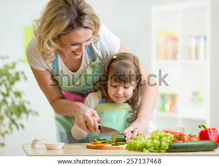 Cute mother teaches child daughter to cook - stock photo