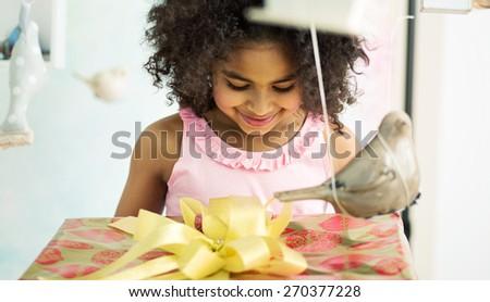 Cute mulatto girl holding a gift - stock photo
