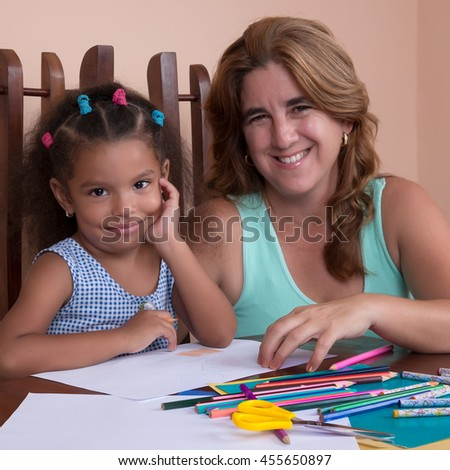 Cute multiracial small girl and her mother drawing with color pencils and smiling