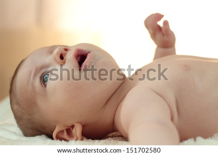 Cute naked baby boy lies on his back - stock photo