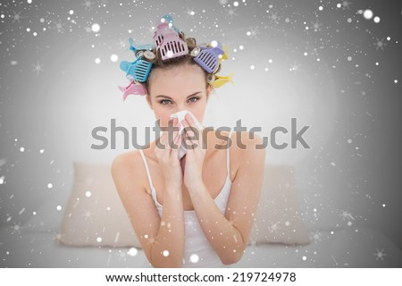 Cute natural brown haired woman in hair curlers sneezing in a tissue against snow - stock photo