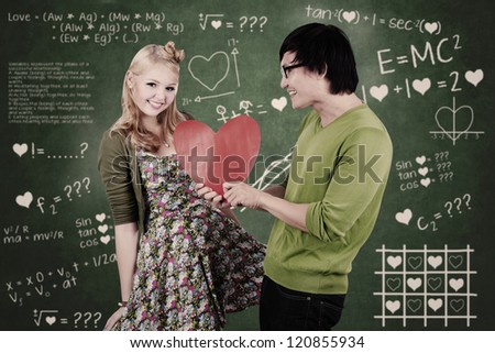 Cute nerd guy is giving his girlfriend Valentine's card in classroom - stock photo
